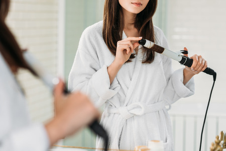 cropped shot of young woman in bathrobe using hair curler at mirror in bathroom