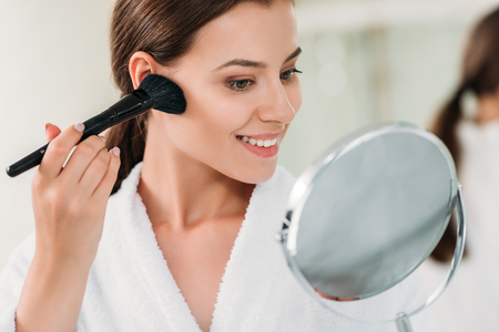 beautiful smiling brunette girl in bathrobe applying powder bronzer with brush