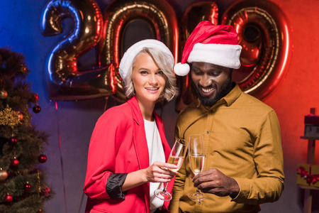 smiling african american businessman and caucasian businesswoman at new year corporate party