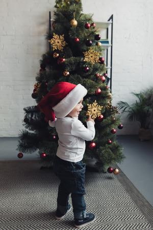 cute smiling boy in santa hat pointing at christmas tree
