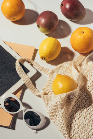 close-up view of digital tablet, sunglasses and string bag with fresh ripe tropical fruits