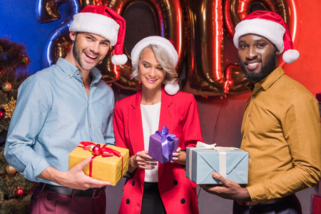happy multicultural businesspeople in santa hats holding presents at new year corporate party Imagens