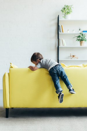 little boy climbing up on yellow sofa at home Stock Photo - 108231732