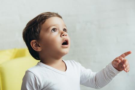 Portrait de petit garçon choqué pointant et levant Banque d'images