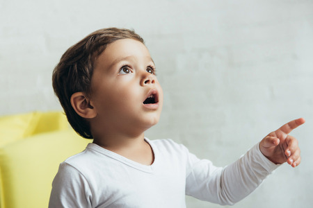 portrait of little shocked boy pointing and looking up
