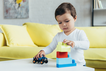 little boy playing with constructor blocks and toy car on table at home