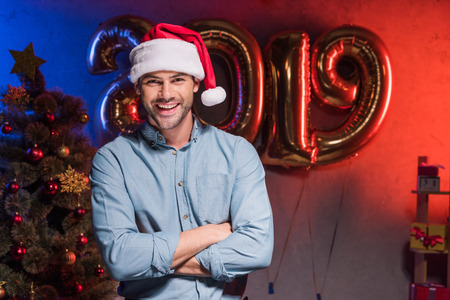 handsome businessman in santa hat standing with crossed arms at new year corporate party Stock Photo