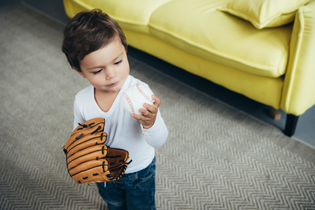 adorable little child playing with baseball glove and ball at home