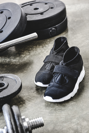 close-up shot of sneakers and weight plates on concrete surface Reklamní fotografie