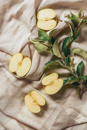 top view of apple halves with apple tree leaves on sacking cloth Фото со стока
