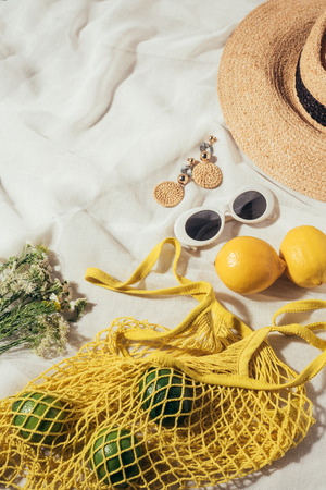 high angle view of straw hat, sunglasses, earrings, flowers and yellow string bag with ripe tropical fruits