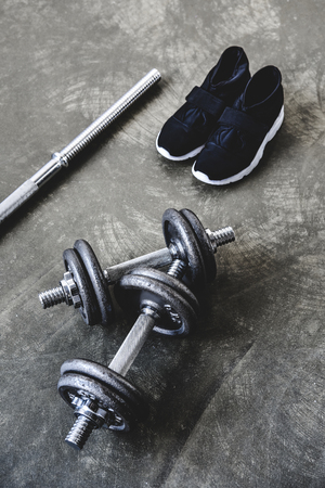 top view of adjustable dumbbells and bar with sneakers on concrete surface