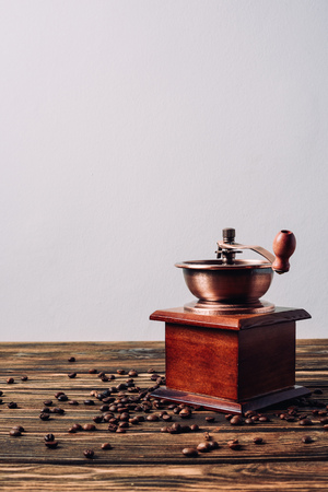 vintage coffee grinder with coffee beans on rustic wooden table Reklamní fotografie