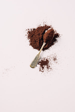 top view of vintage spoon with grinded coffee on white surface