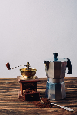 mocha pot and vintage coffee grinder on rustic wooden table