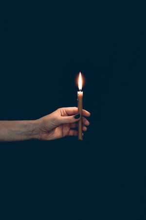 partial view of girl holding flaming candle isolated on black