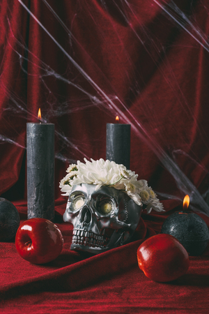 silver skull with flowers, candles and apples on red cloth with spider web