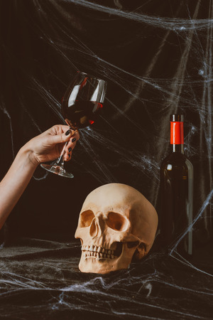 cropped view of woman holding glass of red wine near skull on black cloth with spider web Stock Photo - 108243281