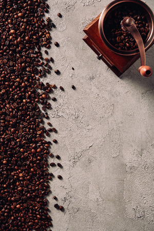 top view of spilled coffee beans with vintage grinder on concrete surface