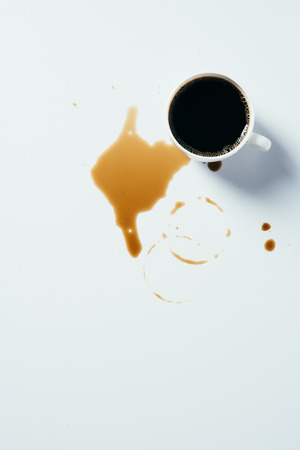 top view of cup of black coffee standing messy on white surface