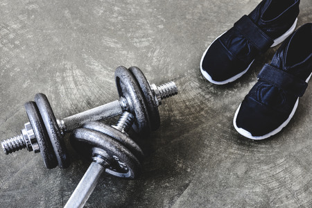 close-up shot of adjustable dumbbells with sneakers on concrete surface 版權商用圖片