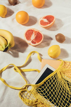 top view of yellow string bag with digital tablet and fresh ripe tropical fruits
