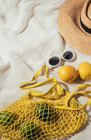 high angle view of sunglasses, wicker hat and string bag with fresh ripe tropical fruits Stock Photo