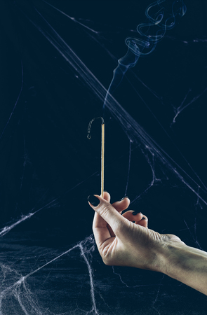 partial view of gloomy woman holding big match with smoke in darkness with spider web