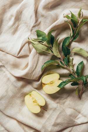 two halves apple with apple tree leaves on sacking cloth