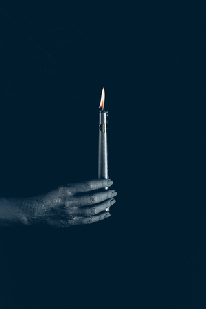 cropped view of black hand with flaming candle, isolated on black