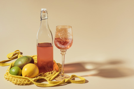 close-up view of drink in glass and bottle, string bag and fresh fruits on brown Stock Photo
