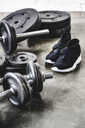 close-up shot of dumbbells and barbell with weight plates and sneakers on concrete floor
