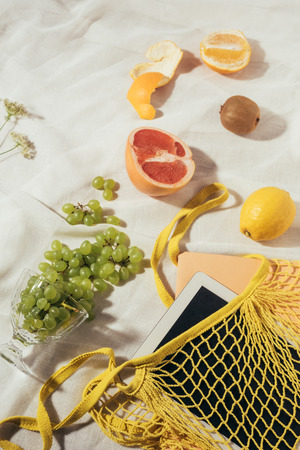 top view of string bag with digital tablet and fresh ripe fruits Stock Photo