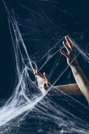 cropped view of gothic woman with hands in spider web in darkness