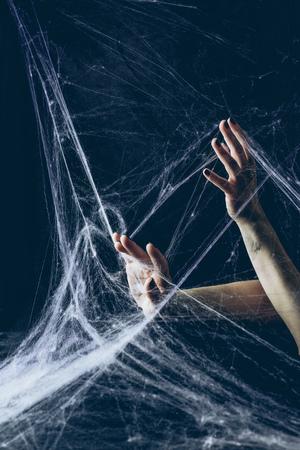 vue recadrée de la femme gothique avec les mains en toile d'araignée dans l'obscurité