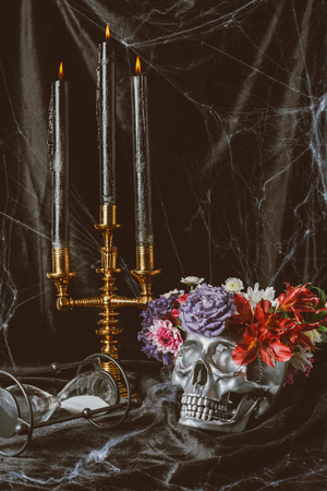 hourglass, silver skull with flowers and candelabrum with candles on black cloth with spider web, decorations for halloween Stock Photo