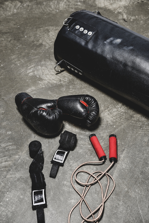different boxing equipment lying on concrete surface