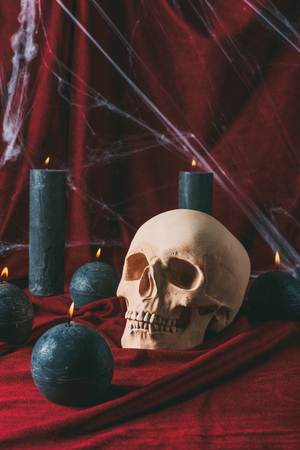 skull and black candles on red cloth with spider web for halloween