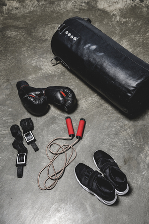 high angle view of various boxing equipment lying on concrete surface