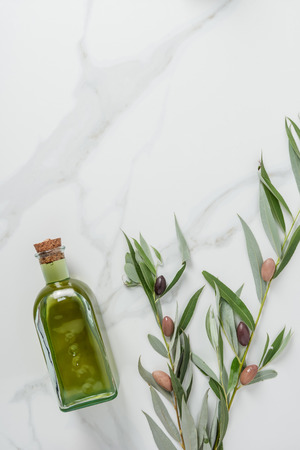 top view of bottle of homemade olive oil and twigs with olives on marble table