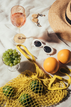 top view of wicker hat, sunglasses, earrings, glass with summer beverage and string bag with fresh fruits