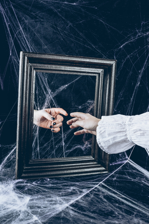 cropped view of woman touching to reflection in mirror with scary spider web around