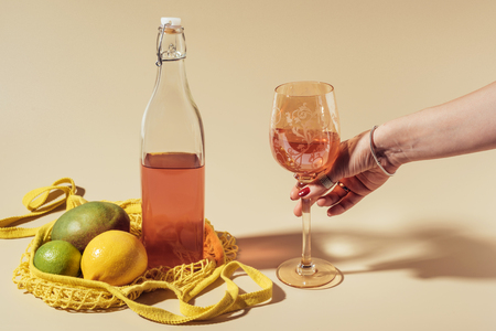 cropped shot of person holding glass with beverage, bottle and string bag with fruits on brown Stock Photo