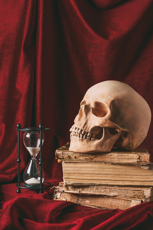 halloween skull on ancient books with hourglass on red cloth Stock Photo