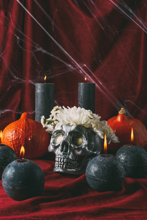 silver halloween skull with flowers, black candles and pumpkins on red cloth with spider web