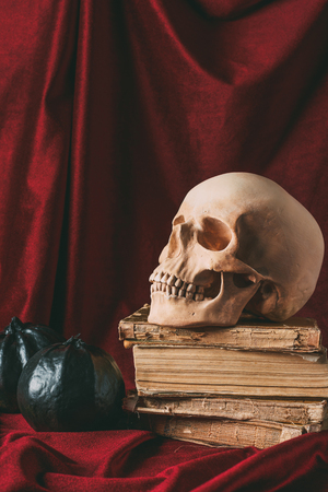 halloween skull on ancient books with black pumpkins on red cloth