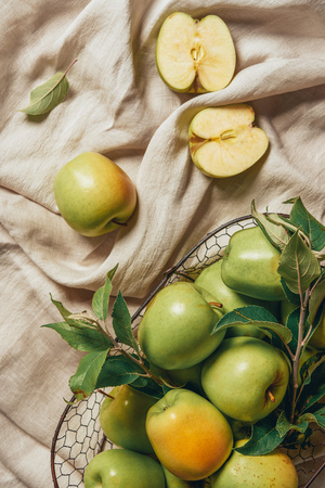 top view of organic apples in metal basket with leaves on sacking cloth Фото со стока