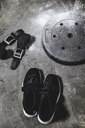sneakers with wrist wraps and weight plate covered with talc on concrete surface