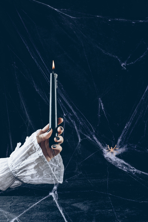 partial view of creepy woman holding black candle in darkness with spider web