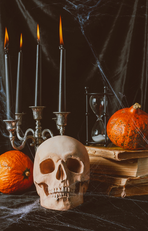 skull, hourglass, pumpkins, ancient books and candelabrum with candles on black cloth